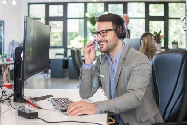 Lächelnder Kundendienst-Betreiber, der Headset trägt und mit dem Kunden spricht, während er am Computer im Büro arbeitet – Foto