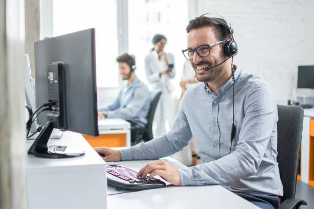 Smiling customer support operator with hands-free headset working in the office. stock photo