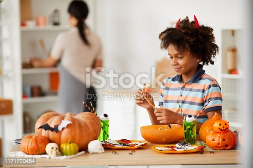 Smiling cute black boy with devils horns standing at counter with various Halloween candies and eating marmalade worm