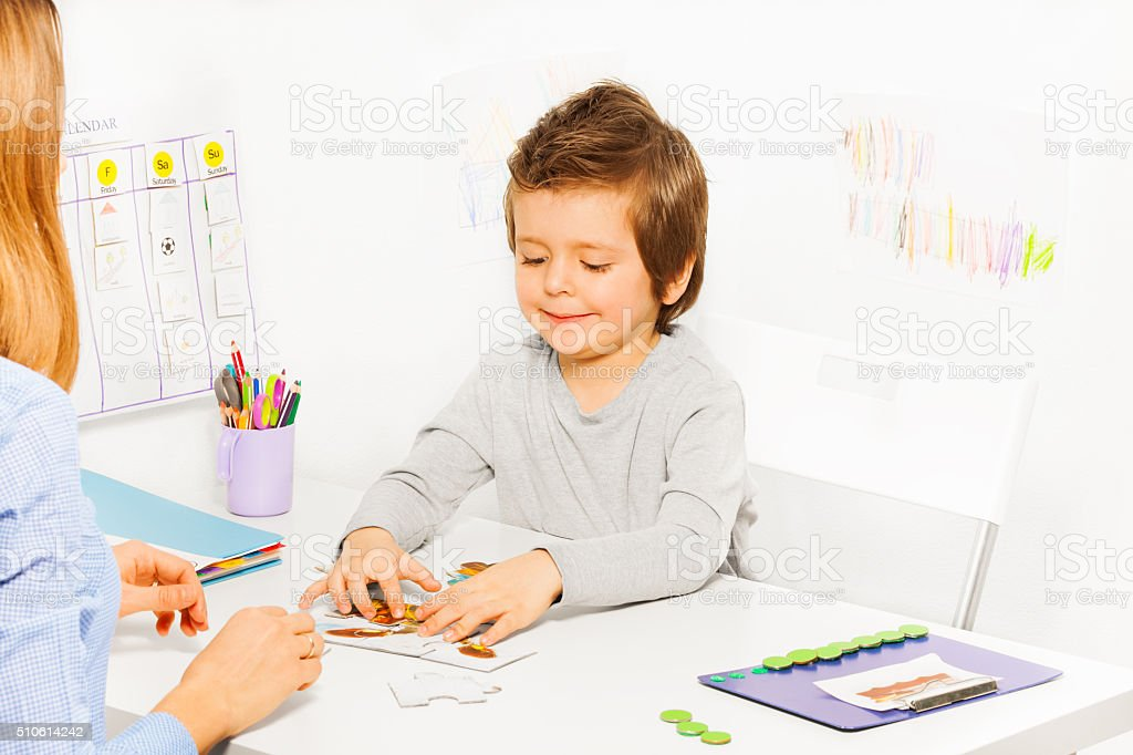 Smiling cute boy plays developing game with parent stock photo