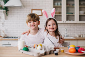 Happy kids hugging each other while looking at camera indoors. They are situating near the table with Easter eggs and paintbrushes