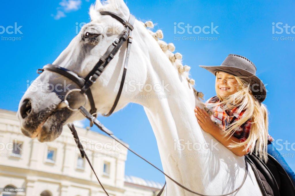 笑顔のかわいいカウボーイの女の子彼女の白を競走馬に寄りかかっ
