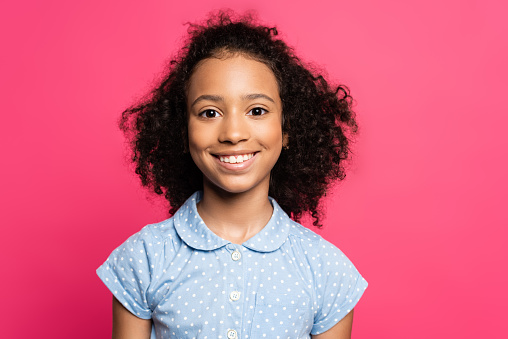 smiling cute curly african american kid isolated on pink