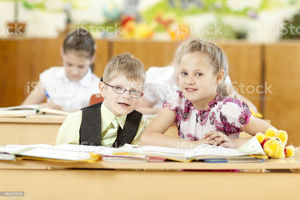 Smiling cute girl and boy in the classroom royalty-free stock photo