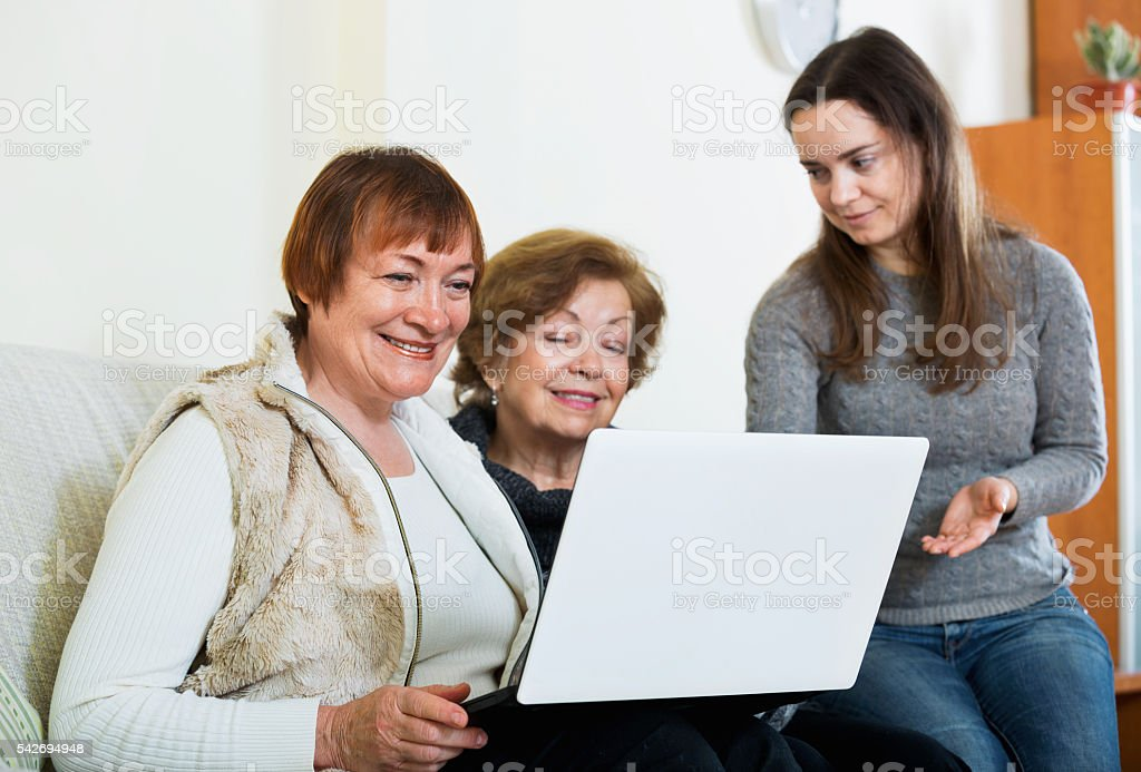 Smiling cute girl teaching positive senior women using laptop stock photo