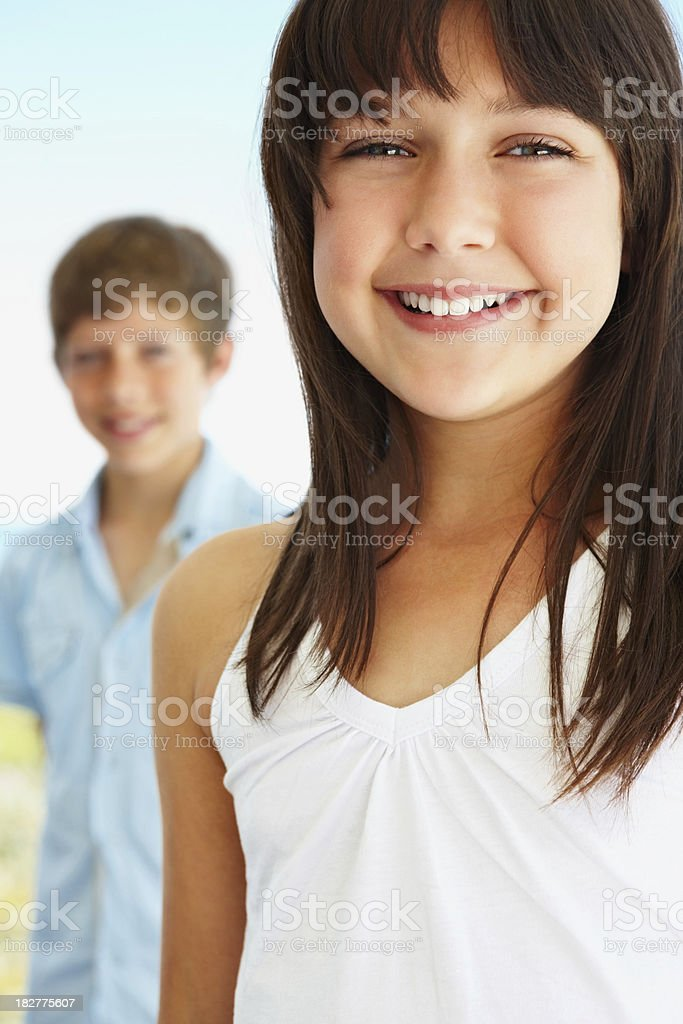 Smiling cute girl with boy in the background royalty-free stock photo