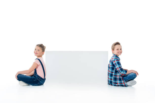 8058b9f8faab Smiling cute kids sitting with blank banner and smiling at camera stock  photo