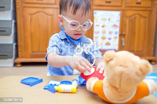 Cute little Asian 2 years old toddler baby boy child playing doctor with plush toy at home, kid holding stethoscope examine teddy bear toy, role play idea for kids concept, photo in real life interior