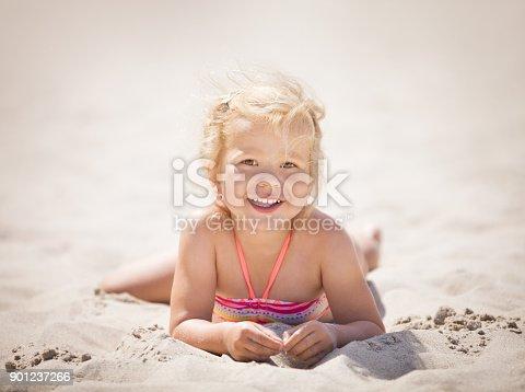 604367022 istock photo Smiling cute little girl lying down on beach 901237266