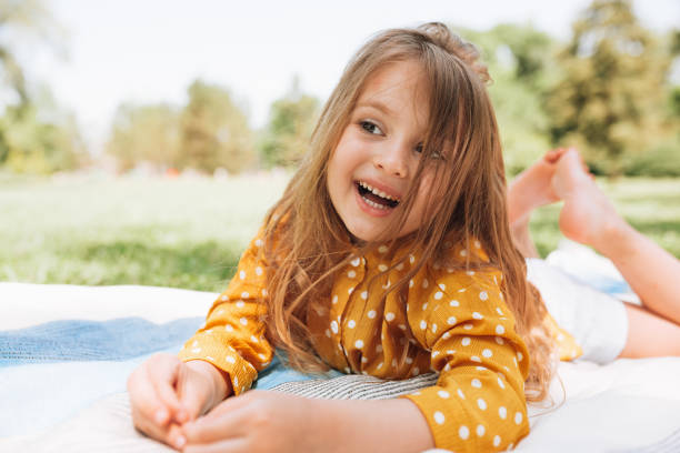 Smiling cute little girl lying on the blanket at green grass, talking with her parents. Adorable child having fun outdoors during picninc with family in the park. Happy childhood concept. stock photo