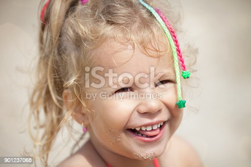 604367022 istock photo Smiling cute little girl on beach with sand on face 901237068