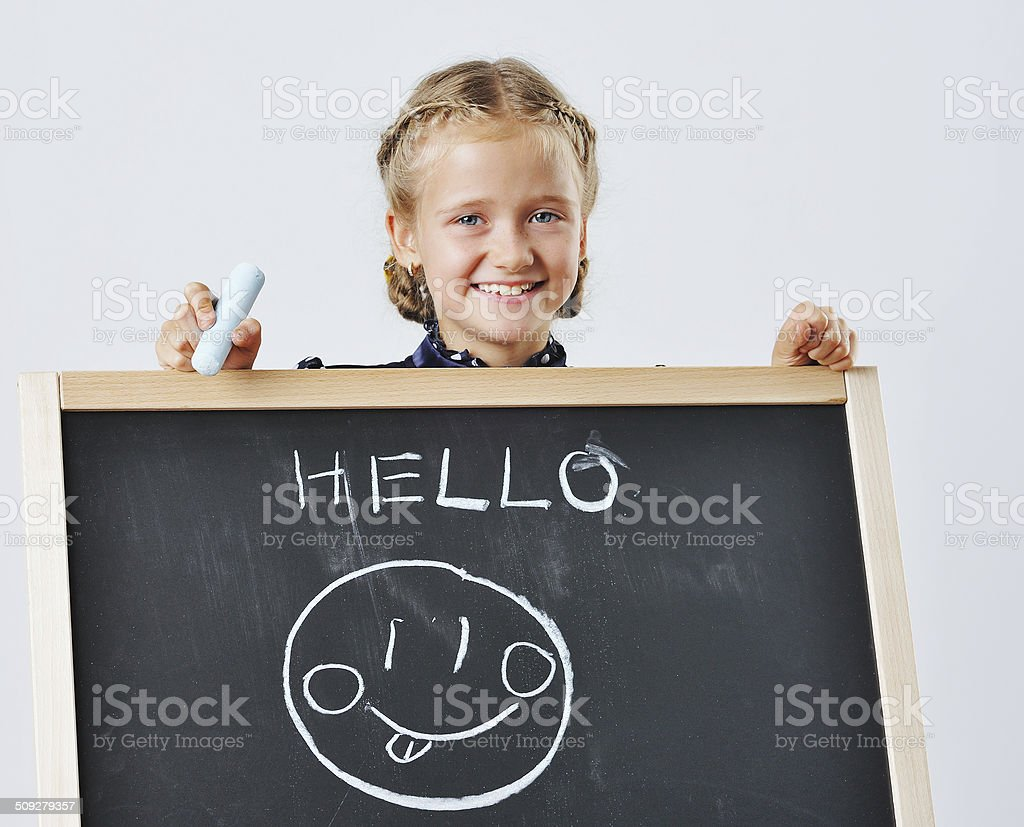 Smiling cute school girl drawing stock photo
