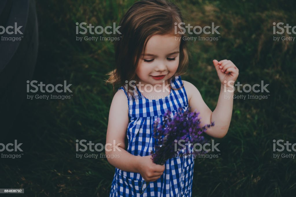 Smiling cute toddler in a field. stock photo
