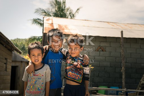 Boneoge,  Indonesia - August 31, 2014: Portrait of three smiling boys with poor clothings in the shanty village of Boneoge, Central Sulawesi, Indonesia. Concept of poverty and childhood in develping countries.