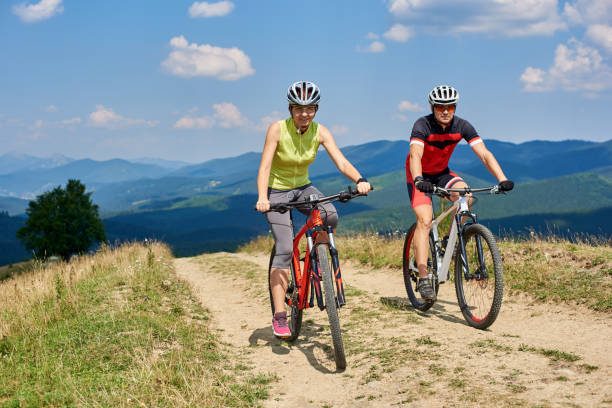 Smiling cyclists couple man and woman in sportswear and helmets cycling cross country bikes Smiling cyclists couple man and woman in professional sportswear and helmets cycling cross country bikes on the mountain road on bright sunny summer day. Active lifestyle and happy relations concept female biker resting stock pictures, royalty-free photos & images