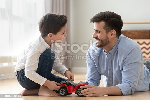istock Smiling dad and son playing racing cars at home floor 1159765848