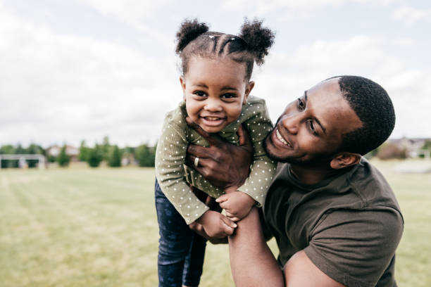 Smiling dad having best time with baby daughter outdoor stock photo