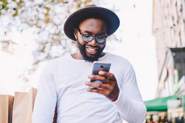 Smiling dark skinned african american hipster guy in hat reading income message on smartphone walking on street, cheerful african american tourist satisfied with 4G connection in roaming via mobile stock photo