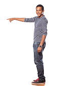 istock Smiling dark-skinned young man in jeans showing a direction 531643917