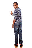 istock Smiling dark-skinned young man in jeans showing thumbs up 531642727