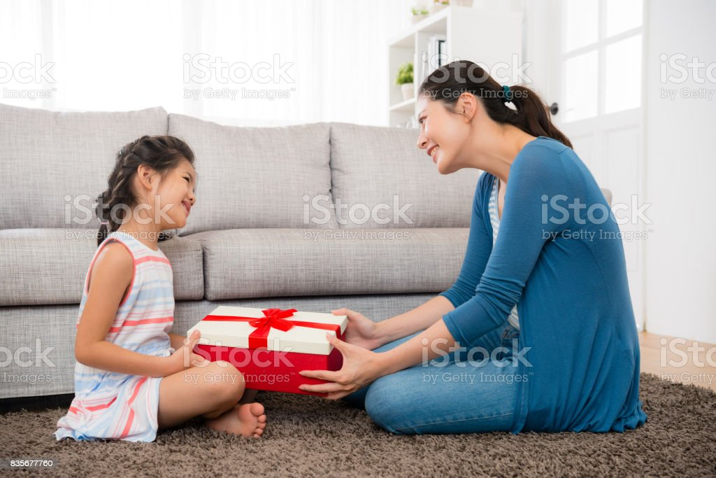 smiling daughter gave her mother a red gift box stock photo