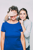 Closeup of smiling young woman looking at camera, showing silence gesture and covering her senior mother eyes. Isolated view on white background.