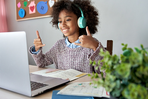 Smiling Deaf African girl signing on a virtual therapy session