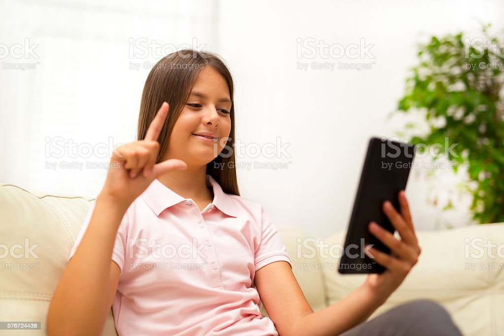 Smiling deaf girl talking using sign language on digital tablet stock photo