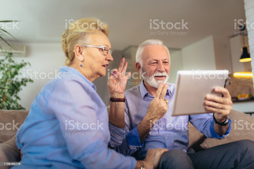 Smiling deaf senior couple talking using sign language on the digital...