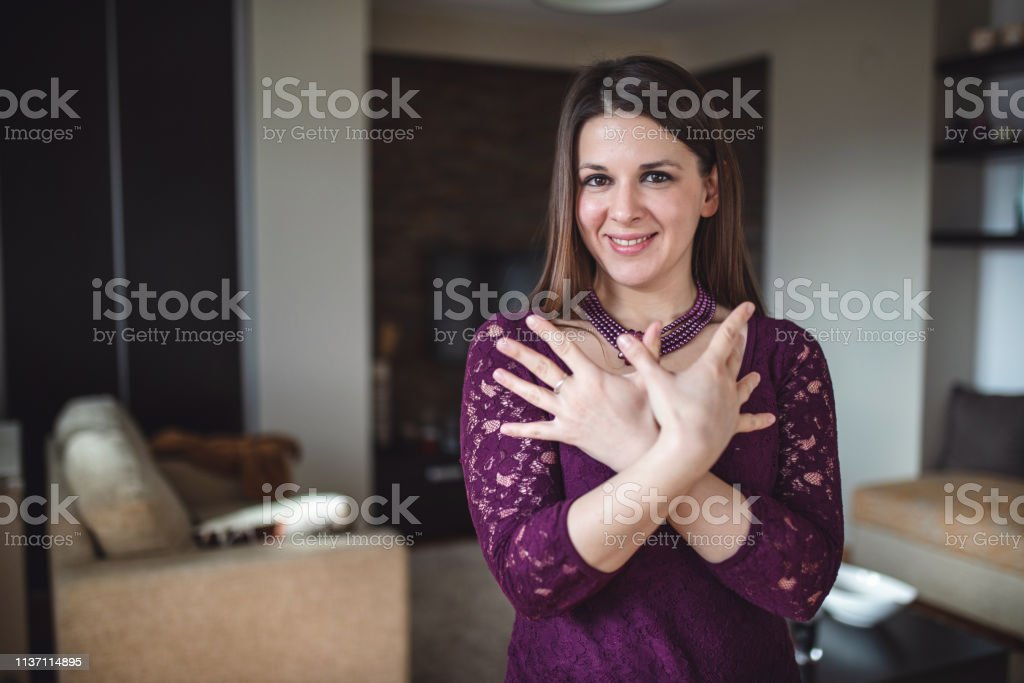 Deaf woman at home doing a sign language.