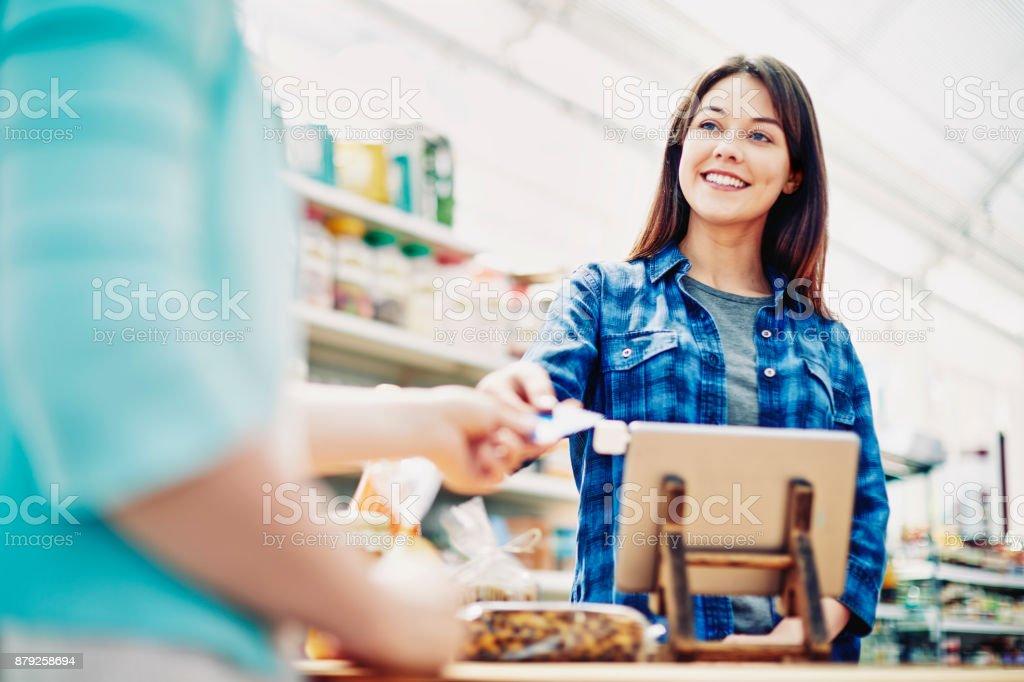 Lächelnd Deli Inhaber empfangenden Kreditkarte vom Kunden im store – Foto
