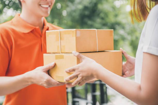 homem de entrega entrega de pacote para uma mulher a sorrir - dia do cliente - fotografias e filmes do acervo