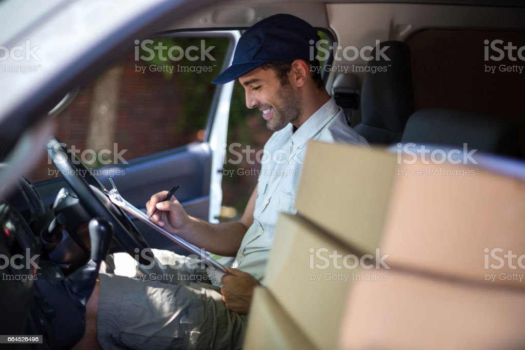 Smiling delivery man writing in clipboard royalty-free stock photo