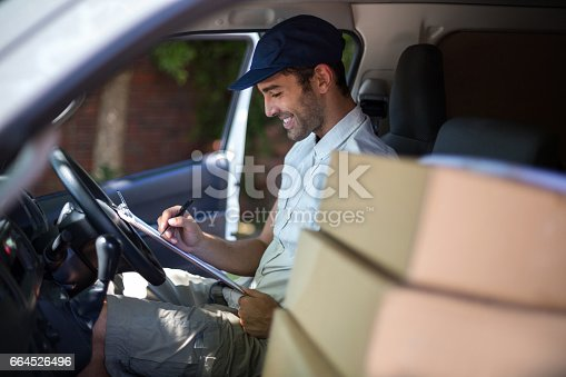 istock Smiling delivery man writing in clipboard 664526496