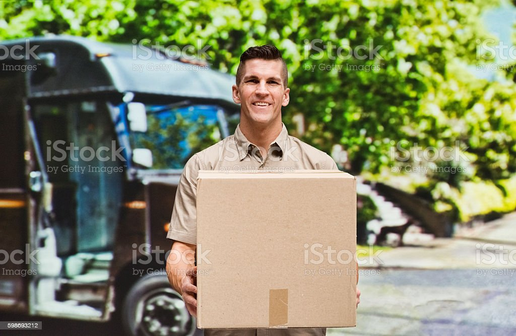 Smiling delivery person holding box outdoors stock photo