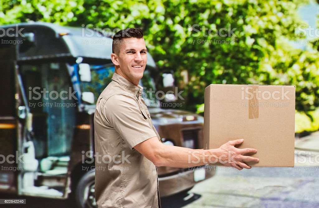 Smiling delivery person holding box outdoors