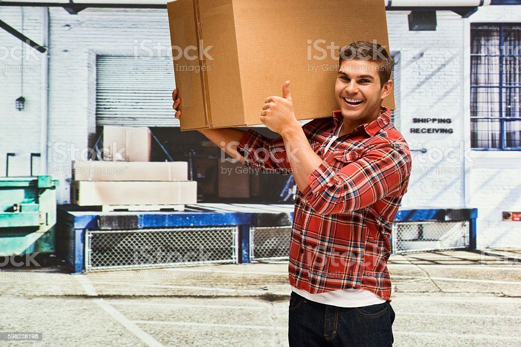 Smiling delivery person thumbs up outdoors foto royalty-free