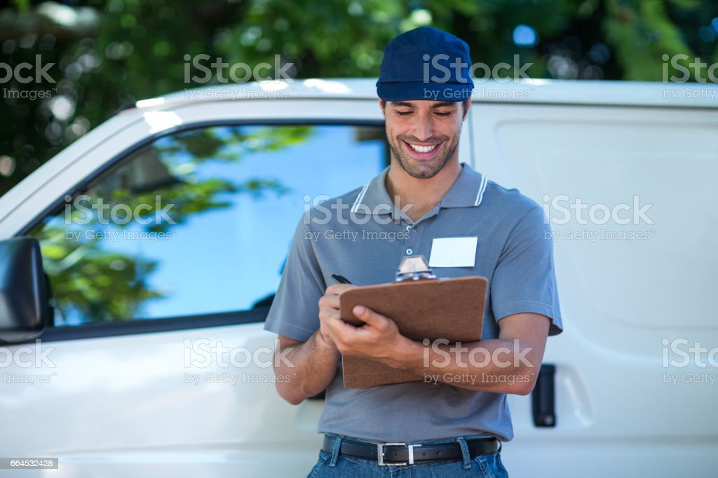 Smiling delivery person writing in clipboard royalty-free stock photo