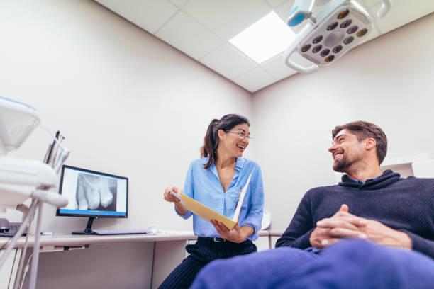 leende tandläkare och patient på tandvårdsklinik - two dentists talking bildbanksfoton och bilder