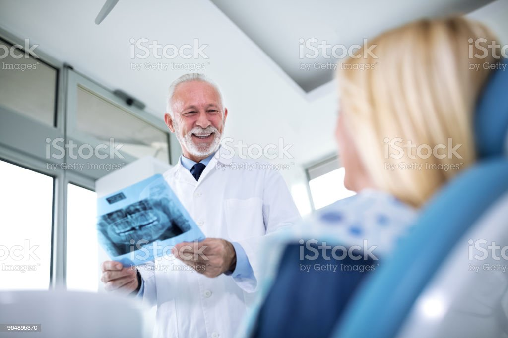 Smiling dentist and patient looking at x-ray of teeth - Royalty-free Adult Stock Photo