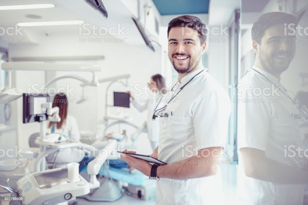 Smiling Dentist With Magnifier Glasses and Digital Tablet in Dental Clinic stock photo