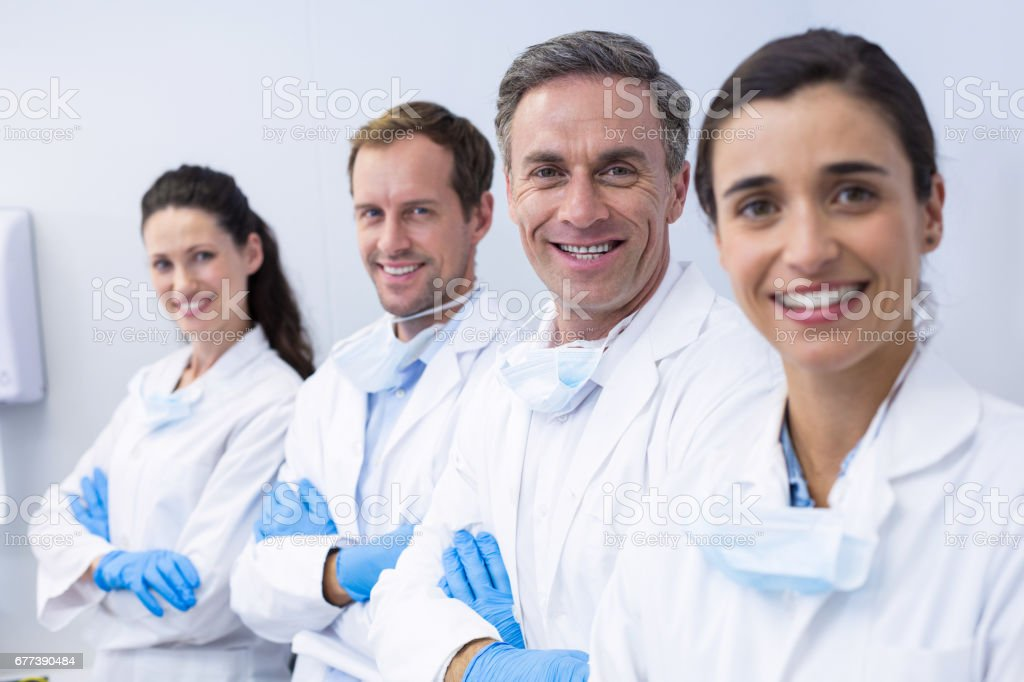 Smiling dentists standing with arms crossed stock photo