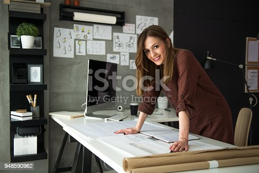 Young smiling female designer standing in front of her designs