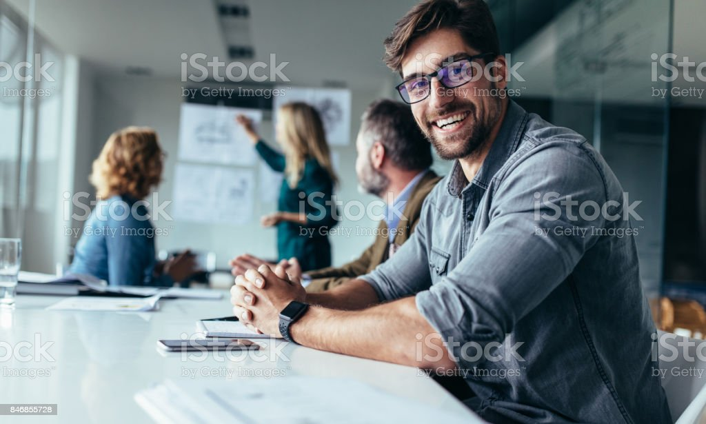 Smiling designer sitting in conference room stock photo