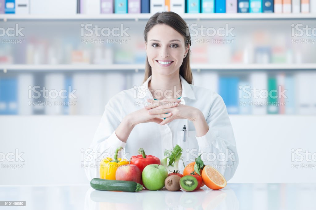 Smiling dietician with healthy vegetables stock photo