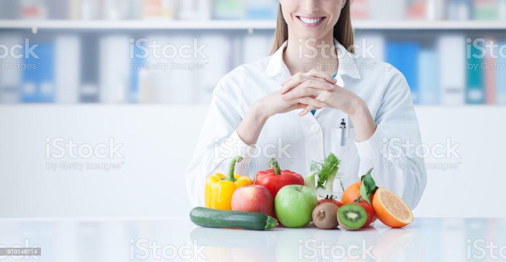Nutricionista com legumes saudáveis a sorrir - foto de acervo