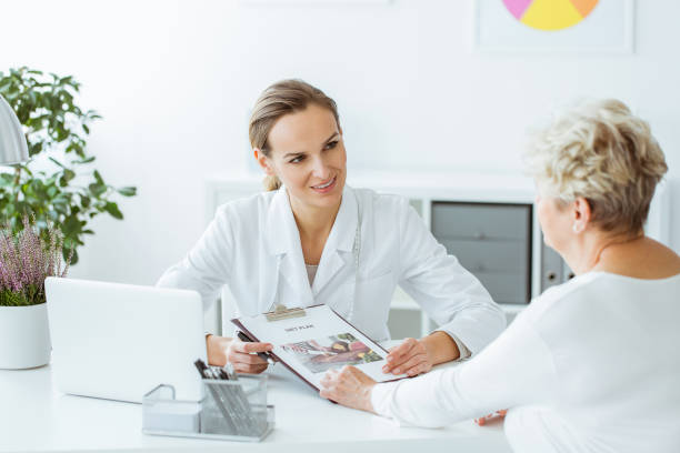 smiling dietitian holding diet plan - dietician stock pictures, royalty-free photos & images