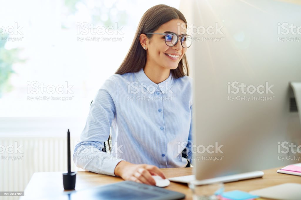 Smiling digital artist working on computer stock photo