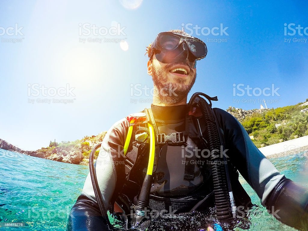 Smiling diver portrait at the sea shore. stock photo