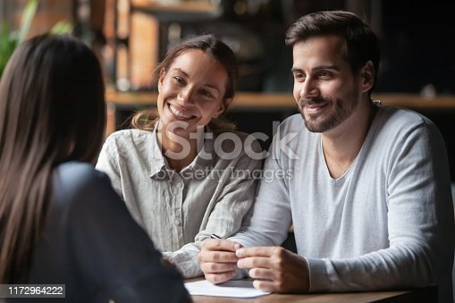 Biracial woman caucasian man listen vacancy candidate sitting together at table at job interview. Diverse couple communicating with real estate agent, successful meeting ready to sign contract concept